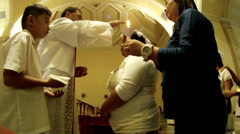 Priest administers Sacrament of Confirmation Stock Footage