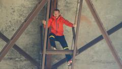 Young man in a red jacket climbs under the bridge support Stock Footage