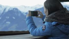 Young woman taking photograph by cellphone in the mountains HD Stock Footage