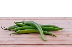 green chillies on chopping board - stock photo