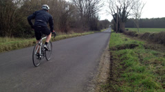 Road bike free wheels past LR - stock footage