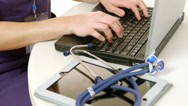 Stock Video Footage of closeup doctor typing on laptop with tablet pc nearby