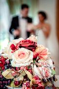 Beautiful bridal bouquet and bride and groom on background, selective focus Stock Photos