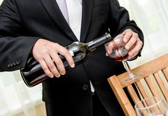 man pouring red wine from bottle into a glass - stock photo