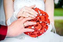 Hands of the bride and groom and bridal bouquet close-up Stock Photos
