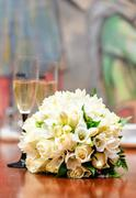 Beautiful bridal bouquet and two glasses of champagne on a background Stock Photos