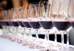 glasses of red wine in a row on a table - stock photo