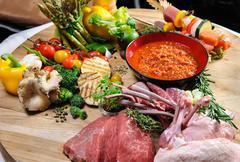 abundance of raw food on a wooden board - stock photo