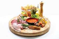 abundance of raw food on a wooden board and basket of bread over white - stock photo