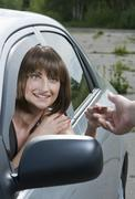 Woman driver shows her license to a police officer Stock Photos