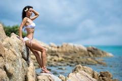 beautiful young woman posing on a rock - stock photo