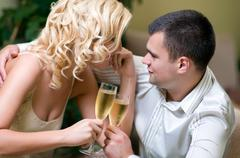 Young couple celebrating with champagne together, in restaurant Stock Photos