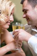 Cheerful young couple drinking champagne in a restaurant Stock Photos