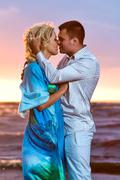 Beautiful young couple in love near the sea at sunset Stock Photos