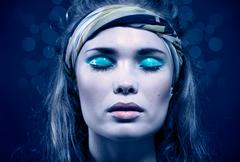 Beautiful young woman with blue make-up Stock Photos