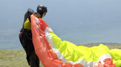 Paragliders landing and taking off from mountain slope near Locarno on August 14 Stock Footage