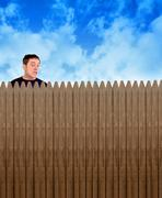 nosey neighbor man looking over fence - stock photo