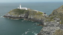 South Stack lighthouse with rotating light and birds flying past Stock Footage