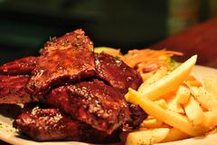 Stock Photo of Spare ribs with french fries and salad