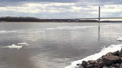 Pan from ice in river to bridge Stock Footage