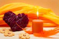 romantic orange background with candle and heart - stock photo