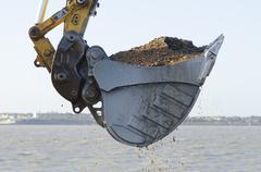 Excavator dredging a harbor Stock Photos