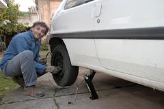 tire puncture, man tighten the bolts until they are seated - stock photo