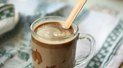 Hand mixing chocolate in a hot milk, preparing hot chocolate or cacao Stock Footage