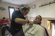 Stock Photo of barber shaving with a razor to young man in a barber's shop