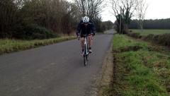 Road bike past fast RL with male rider veer twds camera Stock Footage