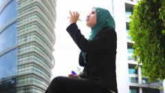 Portrait of young beautiful Muslim wearing Hijab drink water from bottle - stock footage