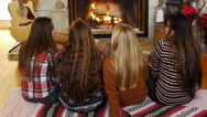 Stock Video Footage of Teen Girls Clink Mugs And Drink Hot Chocolate In Front Of A Fireplace