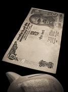 indian currency, 5 (five) rupees & a piggybank - stock photo