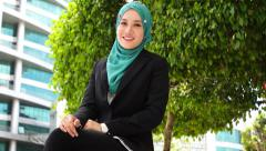 Portrait of young beautiful Muslim wearing Hijab seating and smile at the camera Stock Footage
