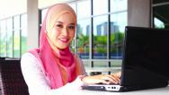 Stock Video Footage of Young muslim girl using laptop and smiling at the camera