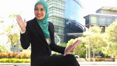 Portrait of young beautiful Muslim wearing Hijab using tablet computer - stock footage
