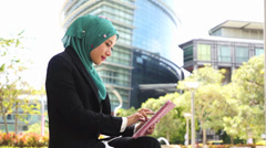Portrait of young beautiful Muslim wearing Hijab using tablet computer Stock Footage