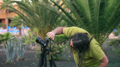 Photographer take pictures  with camera on a tripod Stock Footage