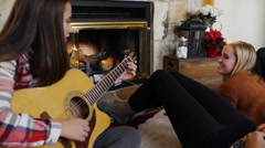 Teen Girl Playing Guitar & Chatting With A Friend In Front Of A Fireplace Stock Footage