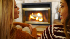 Blonde & Asian Teen Girls Chat, Hug In Front Of A Fire Stock Footage