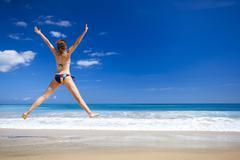 Woman jumping on the beach Stock Photos