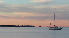 Medium shot of sailboat against pink sky Stock Footage