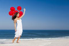 beautiful girl holding red ballons - stock photo
