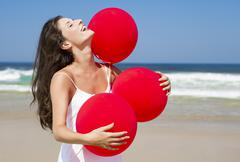 Stock Photo of beautiful girl holding red ballons