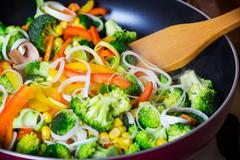 Frying vegetables in pan with spatula Stock Photos