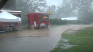 Stock Video Footage of rainstorm at the fair driving rain person walking