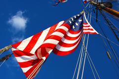 united states flag on the mast of a tall sailing ship. - stock photo