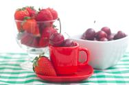 Stock Photo of cherries and strawberry in a ceramic and glass bowl on checkered fabric
