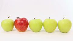 Hand chooses a red apple from a line with green apples, be different - stock footage