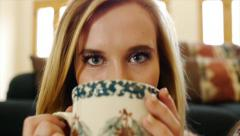 Pretty Blonde Teen Girl Sips Hot Chocolate & Smiles (slow motion) Stock Footage
